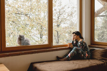 Sleepy, Thoughtful Woman Sitting On The Bed Holding A Cup Of Hot Beverage. Cat Looking At The Camera Through The Glass Window. Domestic Life, Relax, Holiday Concept.
