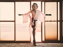 Seductive Slim Androgynous Guy In Elegant Kinky Underwear Leaning On Glass Wall And Looking At Camera