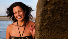 Cheerful Female In Bikini Standing Near Rock On Fuseta Beach And Looking At Camera While Enjoying Summer Vacation At Seaside In Algarve
