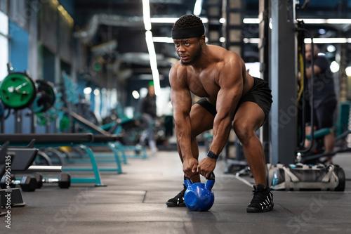 Obraz Muscular shirtless bodybuilder exercising with kettlebell at gym - fototapety do salonu
