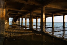 Stone Columns Of Old Pier Above Sea And Wet Fuseta Beach At Sunset In Algarve