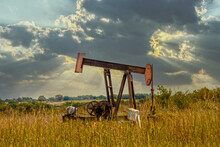 Old Rusty Oil Well Pump Jack In Field - Home Made Modifications - With Field And Cows Blurred In Background And Dramatic Stormy Evening Sky