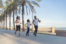African American Family In Sportswear Running Along Street While Smiling And Training Together In Summer
