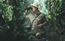 Explorer With Binoculars In The Jungle
