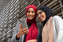 Low Angle Of Arab Female Best Friends In Hijab Standing In Street And Surfing Internet On Smartphone While Laughing And Having Fun