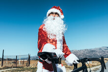 Santa Claus In Red Clothes Standing With Modern Bicycle On Empty Road And Looking Away