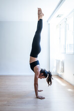 Side View Of Slim Female Athlete Performing Handstand On Wooden Floor In Gym During Training