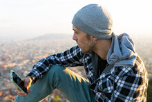 Side View Of Thoughtful Hipster Male Traveler In Warm Checkered Hoodie And Hat With Mobile Phone In Hand Looking Away While Sitting On Hill Against Blurred Town In Autumn Day