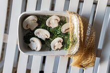 Top View Of Halved Fresh Bio Organic Champignons With Green Herbs In Pot With Eco Sac Placed On White Plank Surface
