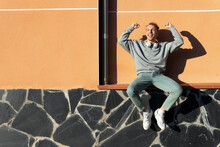 Low Angle Full Body Of Delighted Energetic Young Hipster Male In Casual Clothes With Headphones On Neck Sitting On Bench Near Wall And Raising Arms While Rejoicing Over Good News On Street
