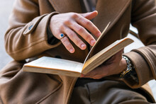 Cropped Unrecognizable Male In Stylish Outfit Sitting Outdoors Reading Interesting Story In Book