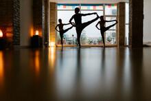 Silhouettes Of Unrecognizable Man And Woman Doing Utthita Hasta Padangusthasana Pose Against Window In Dark Studio