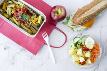 Top View Composition With Delicious Pasta In Foil Box Placed Near Salad Bowl, Fresh Apple And Sandwich With Cheese And Vegetables On Table With Paper Bag Prepared For Takeaway Lunch