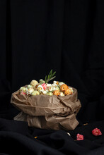 Heap Of Varicolored Sweet Popcorn In Paper Bag Placed With Yellow Corn Seeds On Black Background In Studio