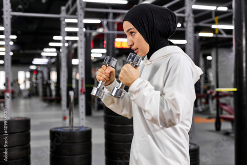 muslim woman in white hijab exercising with dumbbells in gym, enjoying active healthy lifestyle, concentrated on workout, copy space Wallpaper Mural