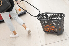 Back View Of Crop Unrecognizable Female Buyer In Cellophane Gloves Carrying Shopping Basket While Doing Purchases In Supermarket During Coronavirus Pandemic