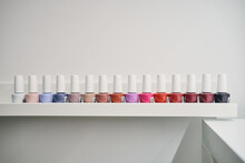 Set Of Colorful Nail Lacquers Placed In Row On Shelf In Modern Beauty Studio