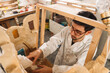 From above of focused male artisan creating facade of clay building while working in art studio