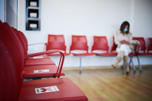 Selective Focus Of Empty Chair With Forbidden Sign For Social Distancing In Clinic Hall With Female Patient In Mask Waiting For Appointment During Coronavirus Pandemic