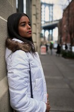 Side View Of Calm African American Female In White Warm Jacket Standing Near Building In New York And Looking Away