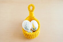 Handmade Crochet Basket With White Chicken Eggs Painted With Flowers Placed On Wooden Table For Easter