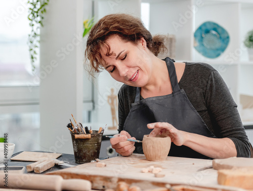 Smiling woman potter working at workshop Wallpaper Mural