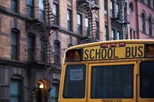 Traditional Yellow School Bus Driving Along Street In New York City On Cloudy Day