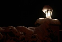 Fence With Illuminated Street Lamp Covered With Snow In Winter In Dark Night