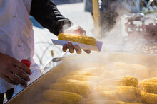 Boiled Sweet Corn For Sale On The Street In Hands Of Seller. Street Fast Food. Baked Corn On Fire.