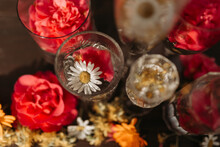 From Above Beautiful Stylish Arrangement With Various Types Of Crystal Glasses And Bottle Placed Among Assorted Fresh Flower Buds On Table Against Blurred Ornamental Background