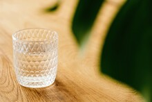 High Angle Of Faceted Glass With Fresh Water Placed On Wooden Table Near Monstera Plant