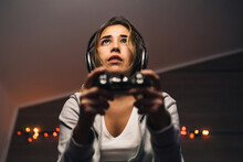 From Below Concentrated Female In Headphones And With Console Sitting In Armchair And Playing Video Game While Entertaining In Evening At Home