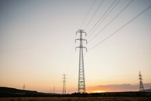 Low Angle Of Tall Electricity Towers And Wires In Field Under Evening Sky With Sun Setting Over Horizon Line In Summertime
