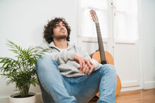 Young Thoughtful Hipster Man In Casual Outfit Sitting On Floor Near Acoustic Guitar And Looking Up While Spending Free Time At Home