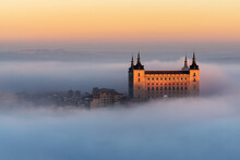 Drone View Of Peaks Of Old Castles Among Dense Clouds At Colorful Sunset With Hills On Horizon In Toledo