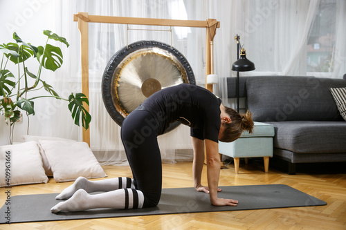Obraz Fit active woman stretching, doing pilates and yoga fitness exercise in room at home. - fototapety do salonu
