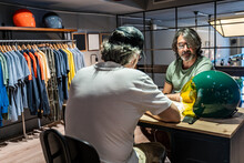 Side View Of Two People Sitting At A Wooden Table While Talking Next To A Motorcycle Helmet Inside A Clothing Store