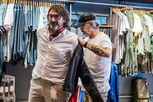 Side View Of A Clothing Store Owner Helping A Customer With Clothes In The Clothing Changing Room Of The Store