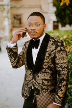Rich African American Male In Posh Tuxedo Standing In Street While Speaking On Smartphone Looking Away