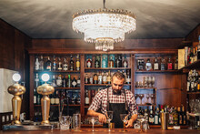 Crop Brutal Male Bartender In Apron Pouring Drink From Bottle In Glass Placed On Counter With Bottles Of Alcoholic Drinks