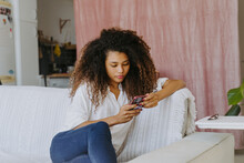 Young African American Female In Casual Outfit Sitting On Sofa And Surfing Internet On Mobile Phone While Resting In Living Room At Home