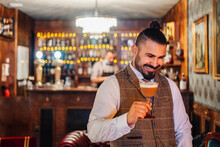 Cheerful Bearded Man Holding Glass Of Irish Coffee Standing Near Old Fashioned Lamp In Classic Room