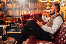 Side View Of Relaxed Bearded Male Using Tablet And Enjoying Liquor While Resting On Sofa In Elegant Pub