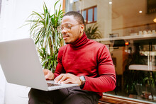 Rich Stylish Focused African American Male Entrepreneur Sitting On Bench Near Cafe Outdoors And Browsing Laptop While Working Remotely On Project