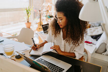 Side View Of Modern Young African American Female Remote Employee In Casual Outfit Sitting At Table With Laptop And Writing In Planner While Working In Home Office