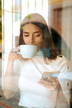 Through Glass View Of Cheerful Young Female Browsing Mobile Phone While Standing Near Window With Cup Of Coffee And Enjoying Free Time At Home