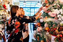 Side View Of Mature Female Friends Buying Christmas Ornaments Inside Decor Shop Looking At Baubles On Christmas Tree