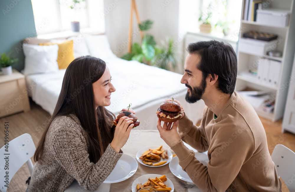 Fototapeta Young couple in love eating hamburgers indoors at home.