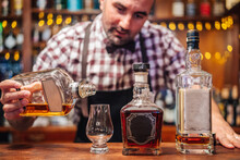 Crop Brutal Male Bartender In Apron Pouring Brandy In Glass Placed On Counter With Bottles Of Alcoholic Drinks