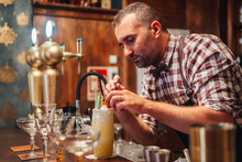 Concentrated Mature Barman In Checkered Shirt Putting Pieces Of Fruit And Ice On Top Of Tropical Cocktail During Work In Bar